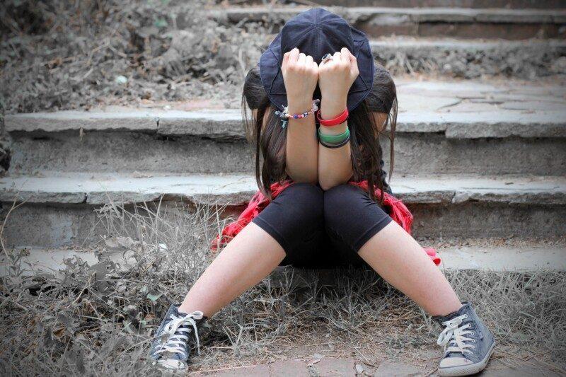 Adolescente con la cara oculta en sus manos
