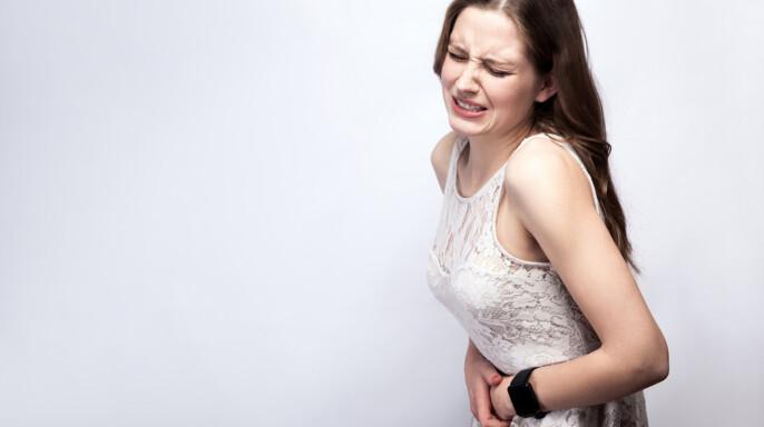 Retrato de mujer hermosa con pecas y vestido blanco y reloj inteligente con dolor de estómago sobre fondo gris plateado. concepto de salud y medicina .