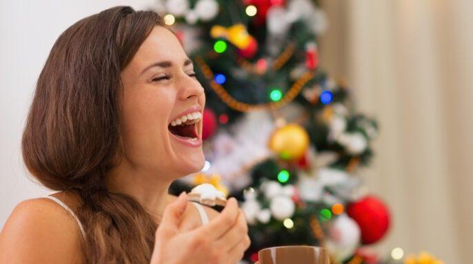 Mujer joven sonriente en pijama comiendo galletas con chocolate caliente