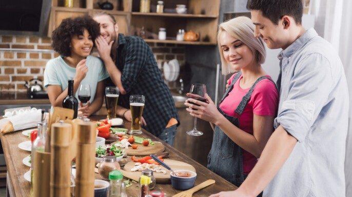 Amigos multiétnicos chismorreando sobre la pareja en la cocina
