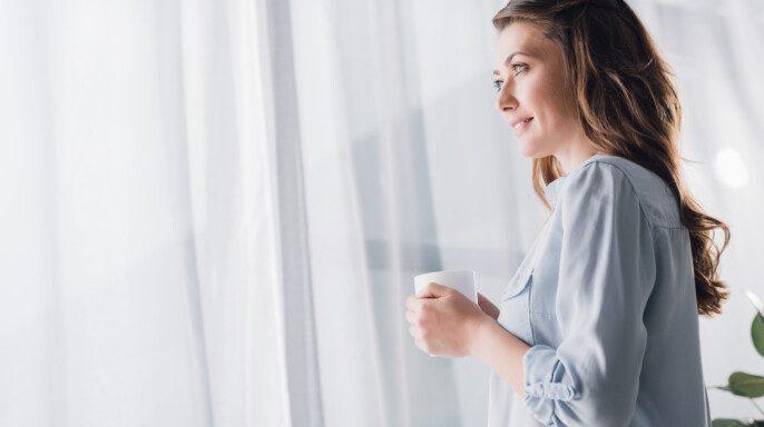 Feliz mujer adulta sosteniendo taza de bebida caliente y mirando hacia otro lado