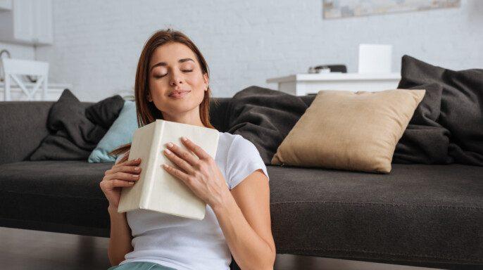 Chica de ensueño sosteniendo libro mientras está sentado en la sala de estar
