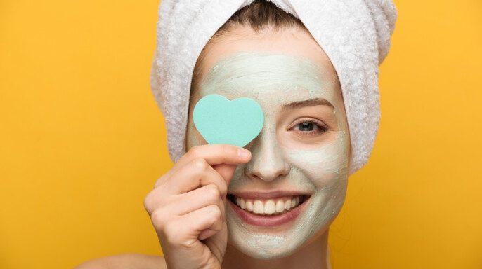 Chica feliz con máscara nutritiva en la cara que cubre los ojos