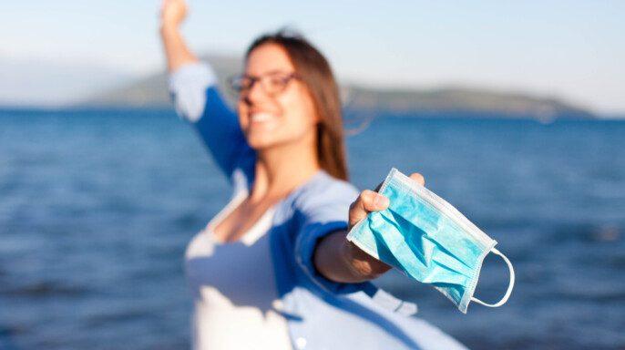 Mujer feliz quitarse la máscara médica en la playa del mar. Corona países libres. Final de cuarentena del coronavirus