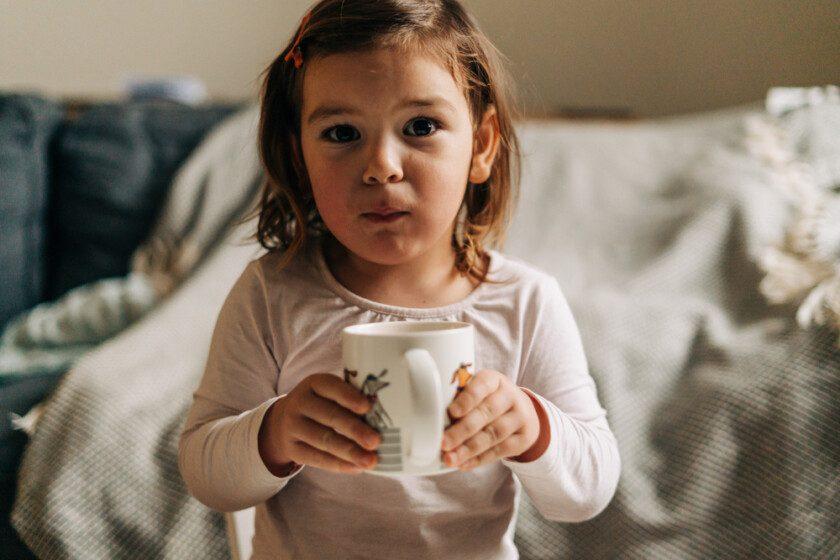 Niña caucásica bebiendo cacao de la taza en casa. Navidad
