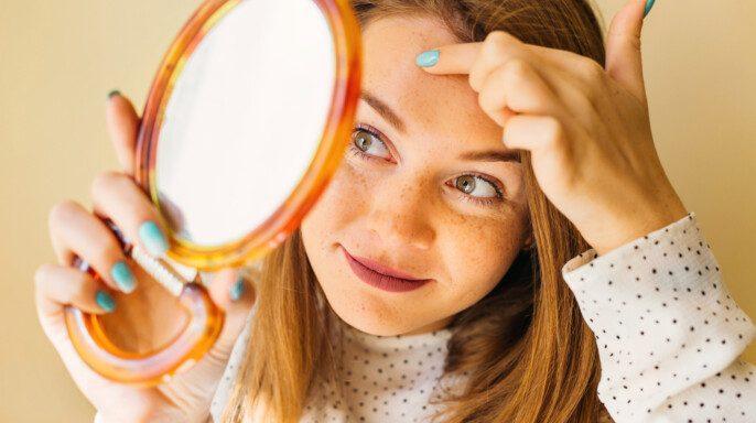 Mujer impactada mirando espinilla en frente en espejo .