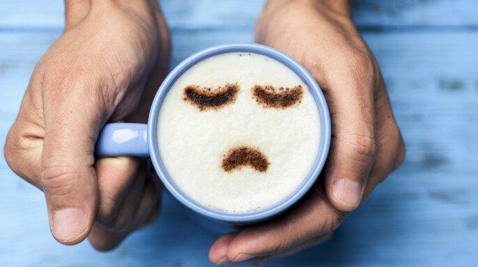 Hombre con una taza de capuchino con una cara triste
