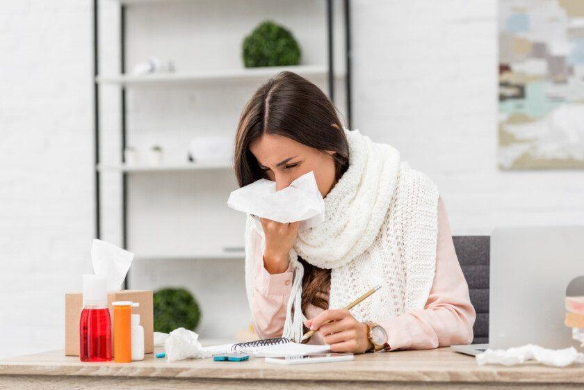 Enferma joven empresaria estornudando con servilleta de papel en el lugar de trabajo