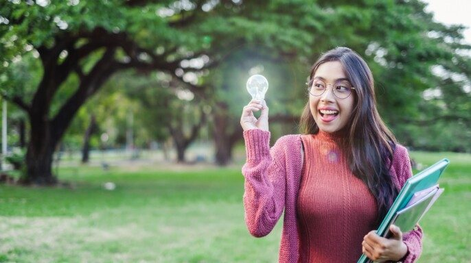 Joven adolescente estudiante sostiene foco concepto de idea