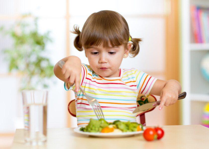 Niño que come alimentos saludables en casa o en el jardín de infantes