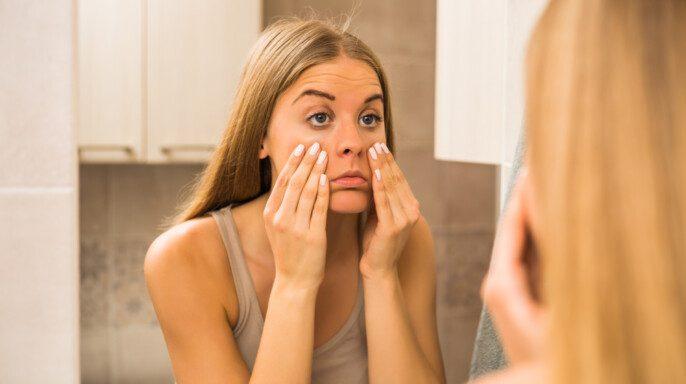 Mujer cansada mirando sus bolsas de ojos en el baño