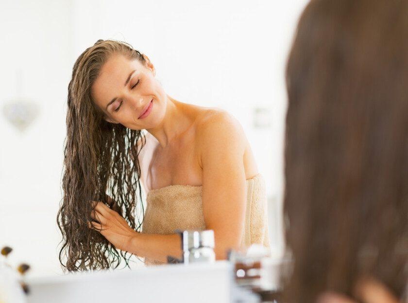 Mujer joven feliz con el pelo mojado en el baño