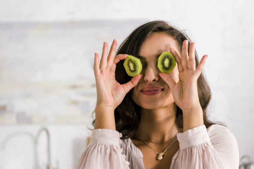 Mujer feliz sosteniendo mitades de kiwi mientras cubre los ojos
