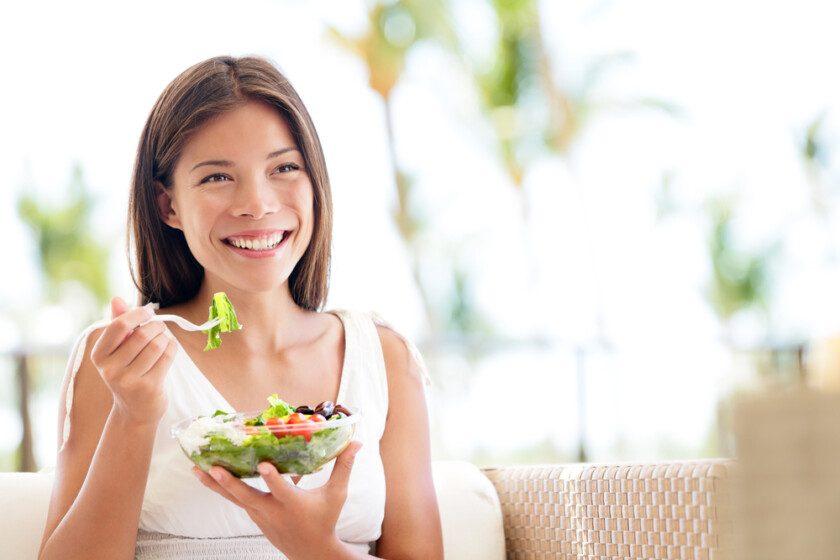 Estilo de vida saludable mujer comiendo ensalada sonriendo feliz