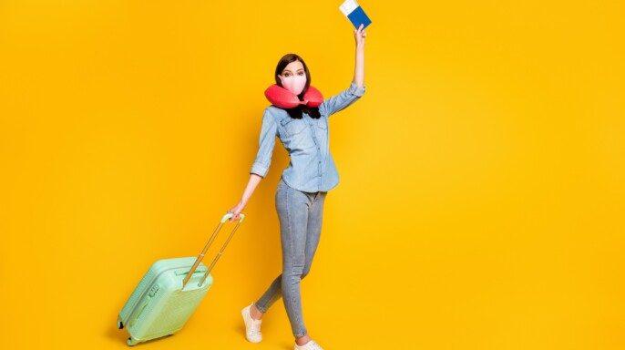 mujer con equipaje y cubrebocas