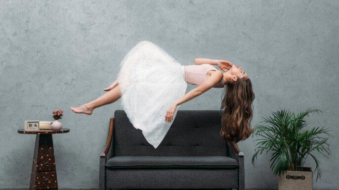 Joven descalza mujer levitando por encima del sofá