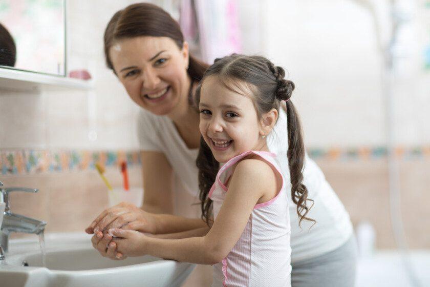 Niña con mamá lavándose las manos en el baño