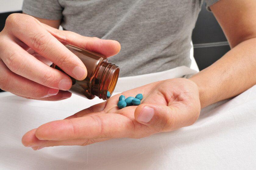 Hombre en la cama a punto de tomar algunas pastillas azules