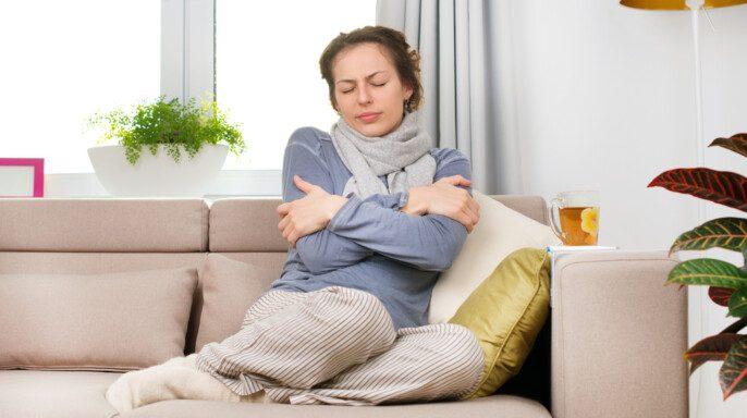 n sentada en sofá con frío Jovem