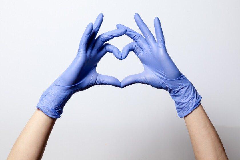 Primer plano de manos en goma de látex haciendo la forma de un corazón