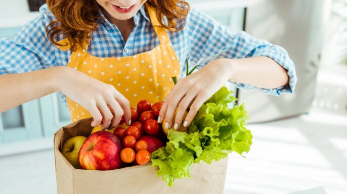 Mujer feliz en lunares delantal amarillo tomando frutas y verduras de la bolsa de papel