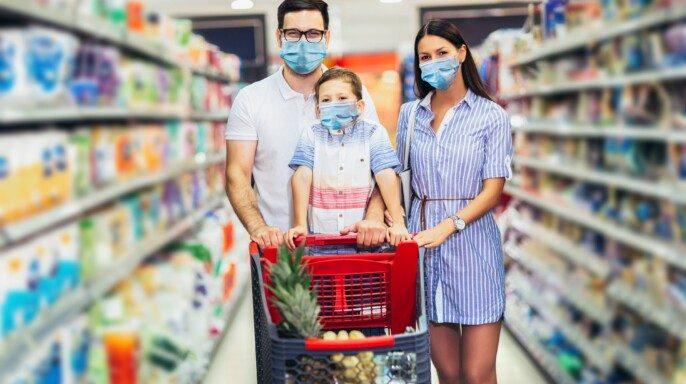 Familia feliz con mascarillas en el súper mercado