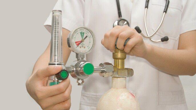 Doctora está ajustando válvula de oxígeno