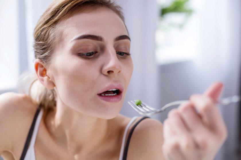 Mujer pálida triste sosteniendo un tenedor