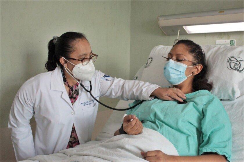 Doctora con estetoscopio atendiendo paciente en cama