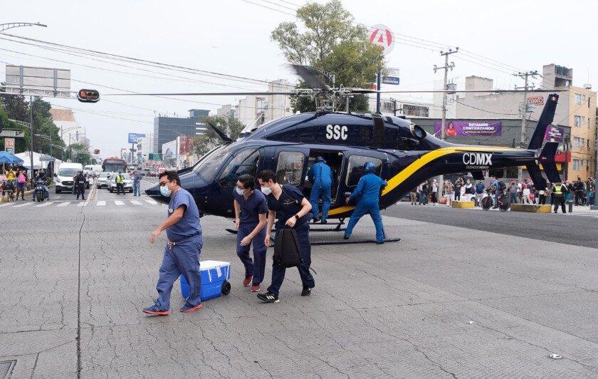 Personal médico trasladando contenedores desde un helicóptero