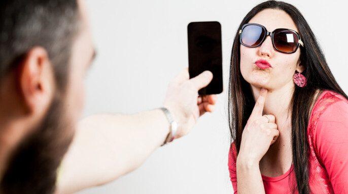 Pareja emocionada tomando fotografías móviles y selfies