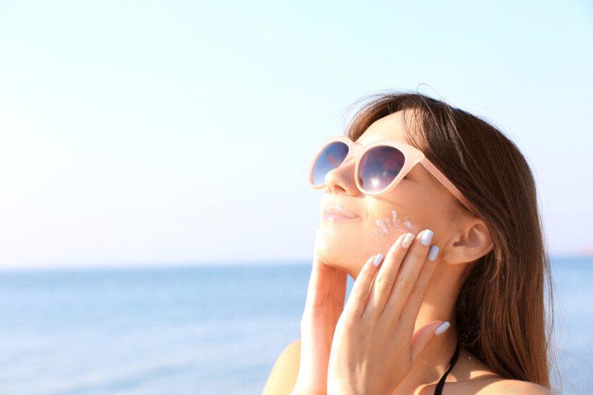 Mujer joven usando protector solar en el fondo del mar