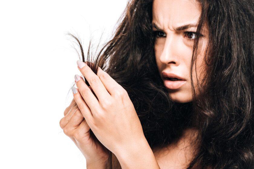 Mujer estresada mirando el cabello seco dañado