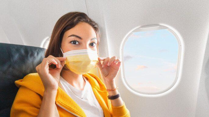 Una chica usa una máscara facial médica durante un vuelo