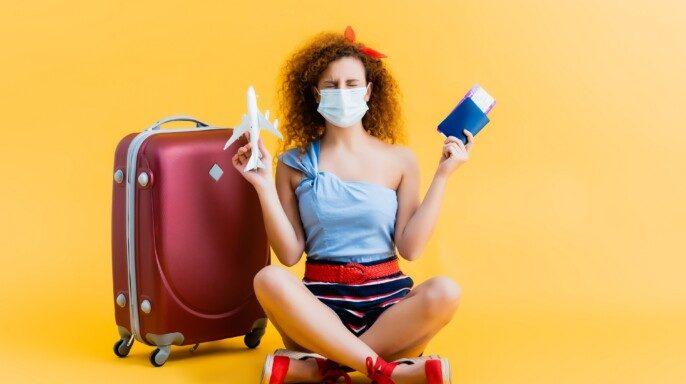 Mujer joven y rizada con máscara médica con pasaporte y avión