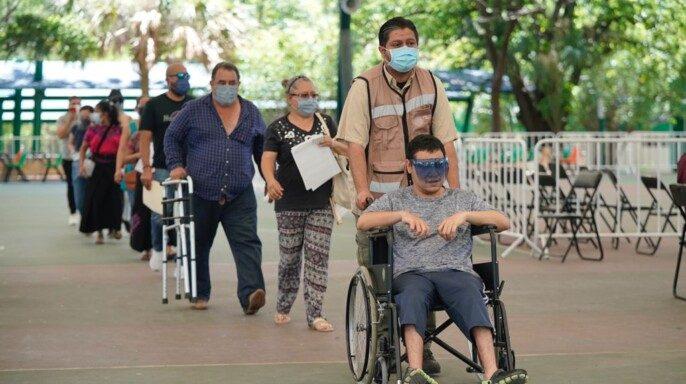 personas en fila para vacunación