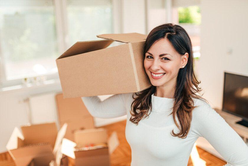 Alegre mujer latina sosteniendo cajas mientras se mueve en nueva