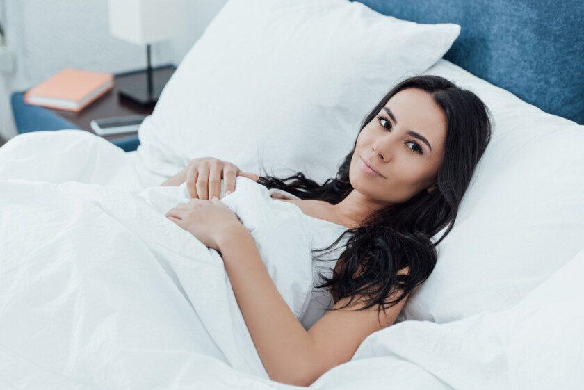 Mujer morena acostada en la cama con sonrisa