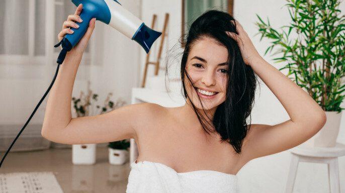 Mujer joven en toalla de baño secado cabello