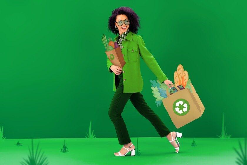Mujer afroamericana sonriente y elegante caminando con bolsas de compras ilustradas con carteles de reciclaje sobre fondo verde
