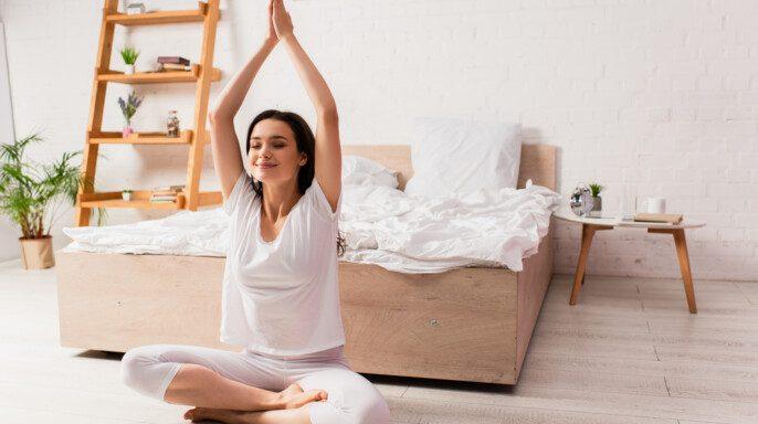 Mujer joven y descalza sentada con las manos por encima de la cama