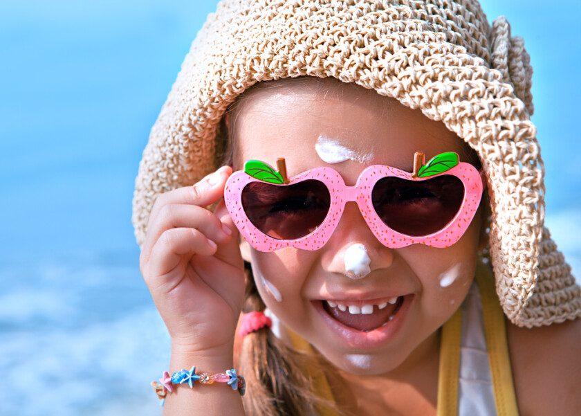 Niña feliz con gafas y protector solar en la cara