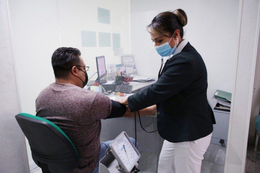 Enfermera del IMSS midiendo presión arterial