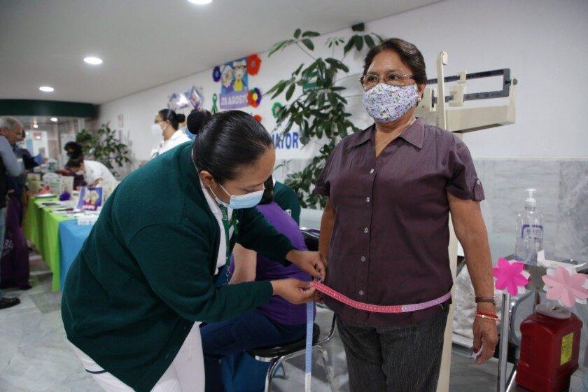 Enfermera midiendo la cintura de adulta mayor