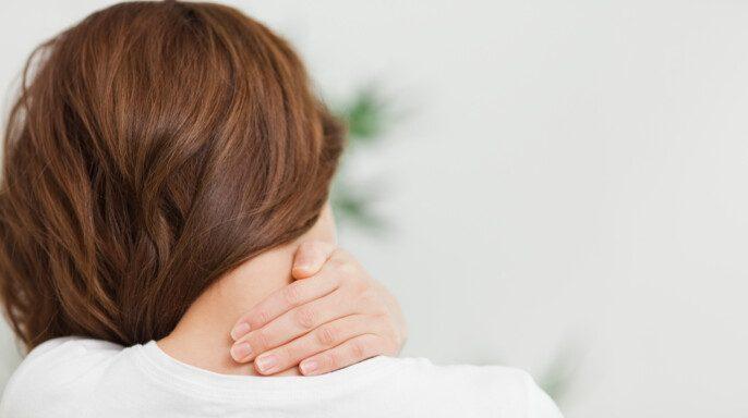 Primer plano de una mujer morena masajeando su cuello