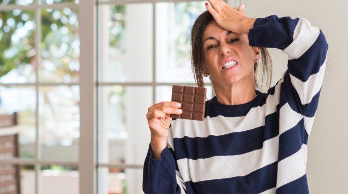 Mujer de mediana edad comiendo barra de chocolate estresada