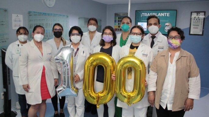 Personal del IMSS sosteniendo globos del número 100
