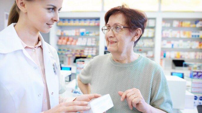 Enfermera asisteindo a ault mayor en farmacia