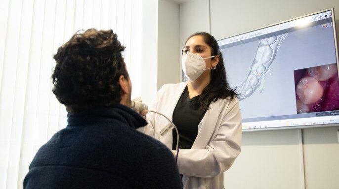Odontologa revisando con equipo digital un paciente