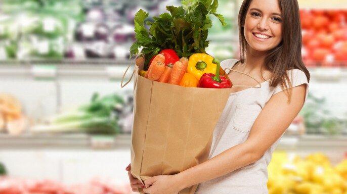 Mujer sonriendo con una bolsa de vegetales en un supermercado